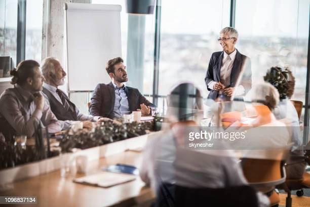 happy female leader giving a speech to large group of business people in a board room. - board room stock pictures, royalty-free photos & images