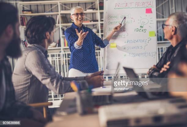 Glücklich Anführerin Vortrag zu ihrem männlichen Team im Büro.