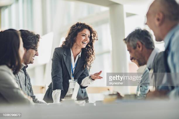 happy female leader talking to her colleagues on a business meeting in the office. - leadership stock pictures, royalty-free photos & images