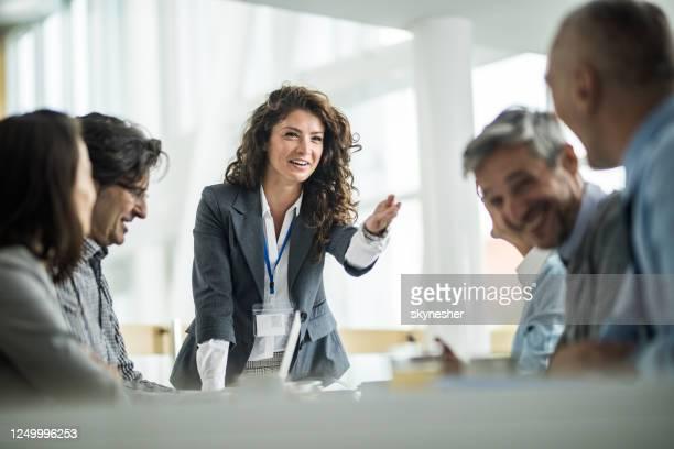 glückliche weibliche leiterin im gespräch mit ihren kollegen auf einem geschäftstreffen im büro. - chef stock-fotos und bilder