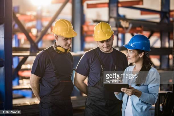 gerente fêmea feliz e trabalhadores manuais que usam o touchpad em uma fábrica. - vestuário de proteção - fotografias e filmes do acervo