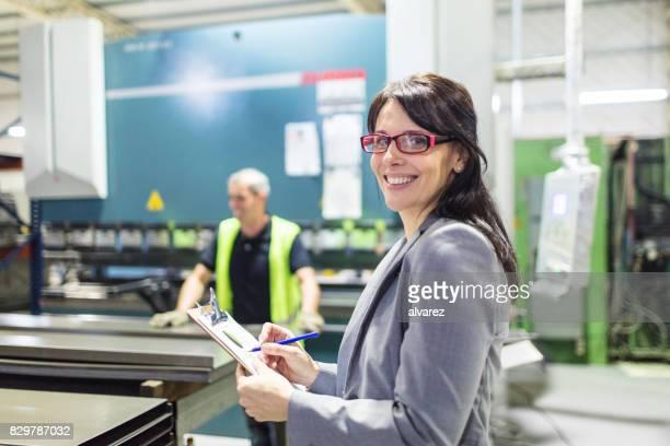 heureux femme gestionnaire avec usine de presse-papiers - personne secondaire photos et images de collection