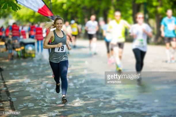 happy female marathon runner running over plastic cups - marathon stock pictures, royalty-free photos & images
