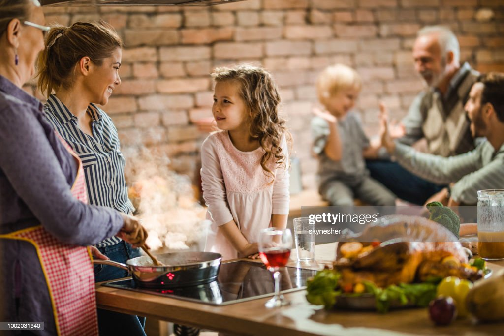 Happy female members of extended family talking while preparing a dish for Thanksgiving. : Stock Photo