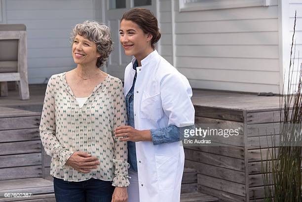Happy female nurse assisting elderly woman in nursing home