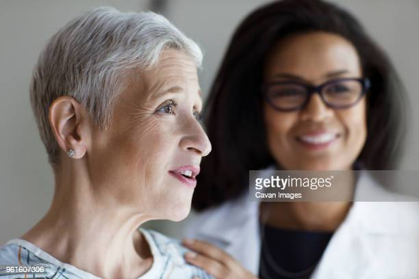 Happy female patient looking away with doctor in background