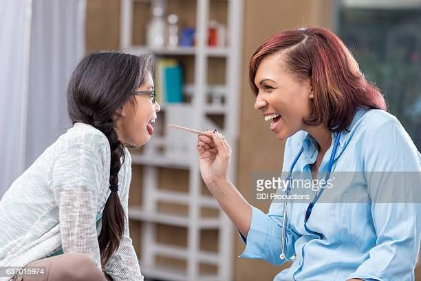 Happy female pediatrician examines young patient