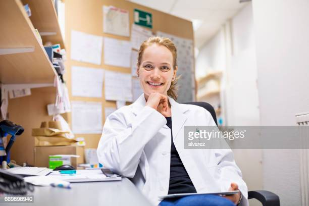 Happy female pharmacist sitting with hand on chin