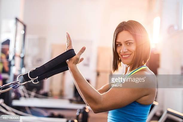 Feliz mujer el ejercicio de Pilates de reformistas en un club de salud.