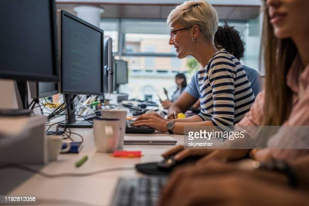 happy female programmer working on desktop pc in the office. - computer equipment stock pictures, royalty-free photos & images