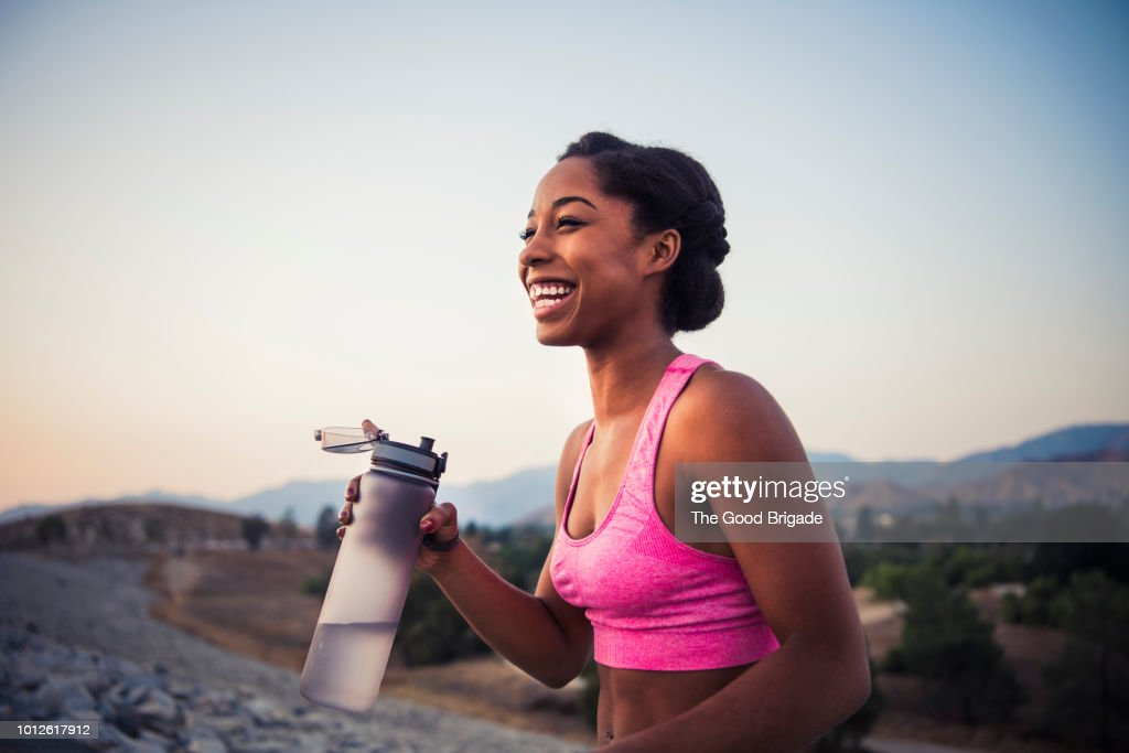 Happy female runner holding water bottle : Stock Photo