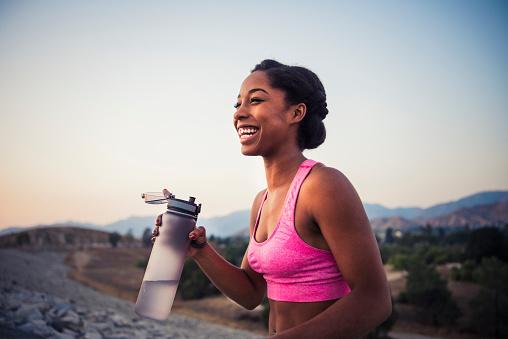 Happy female runner holding water bottle - gettyimageskorea