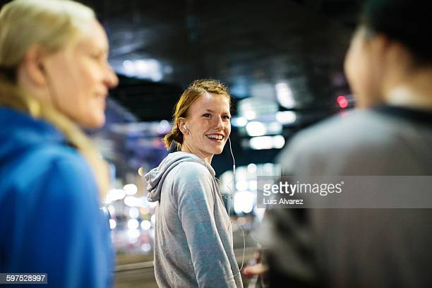 Happy female runner looking at friends in city