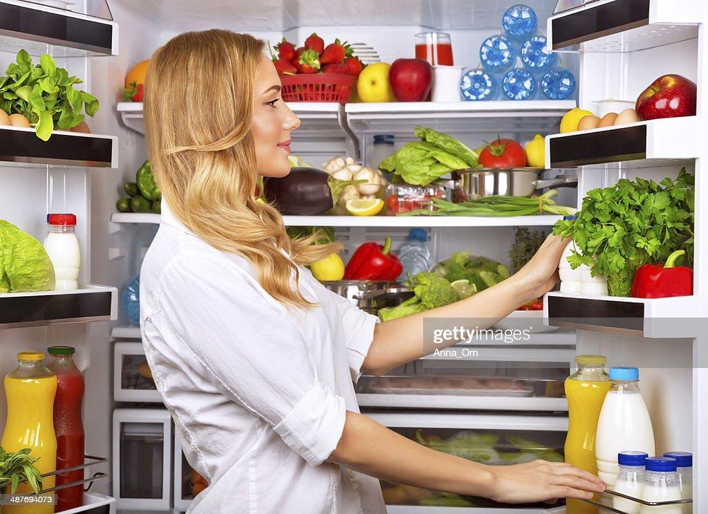 Glückliche Frau suchen Sie sich etwas im Kühlschrank : Stock-Foto