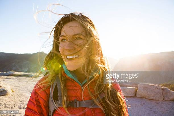A happy female smiles while hiking.