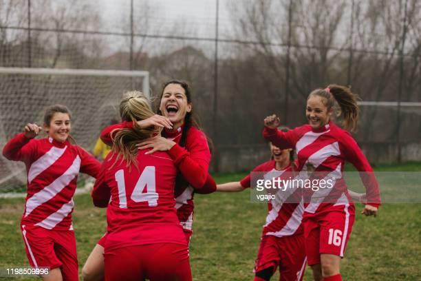 gelukkige vrouwelijke voetballers vieren doel - scoren stockfoto's en -beelden