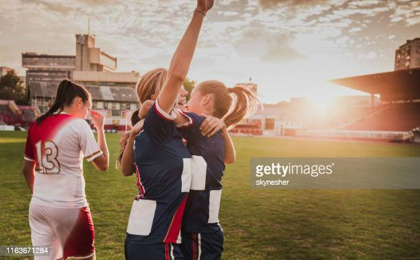 happy female soccer players celebrating their victory on a stadium. - scoring a goal stock pictures, royalty-free photos & images