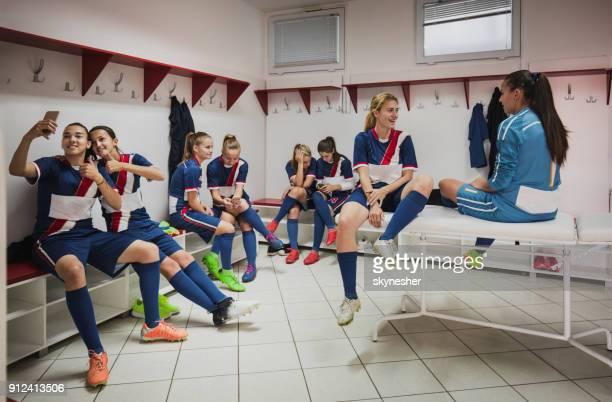 gelukkig vrouwelijke voetballers met behulp van mobiele telefoons en praten in de kleedkamer. - kleedkamer vrijetijdsfaciliteiten stockfoto's en -beelden