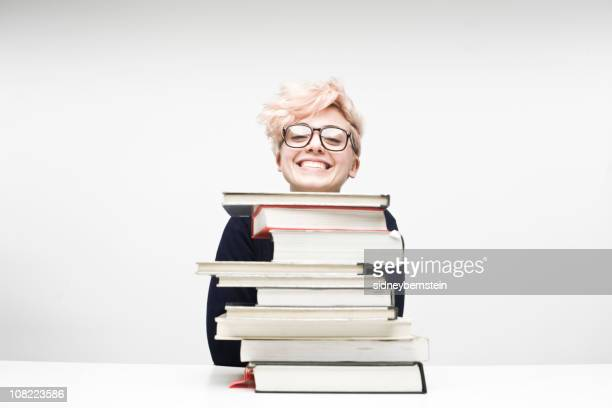 Happy Female Student Sitting Behind Pile of Textbooks