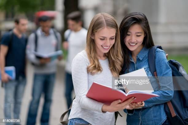 Glücklich Studentinnen im freien lesen Noten auf einem notebook