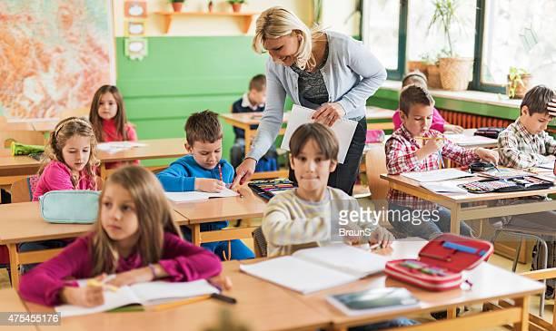 Glücklich weibliche Lehrer Unterstützung von elementaren Schülern im Klassenzimmer.