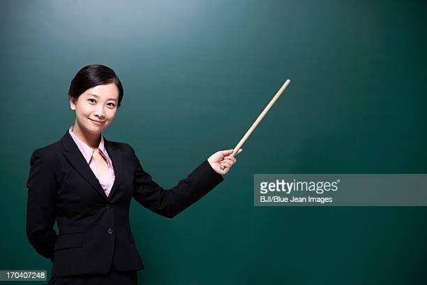 Happy female teacher holding teacher's pointer in classroom