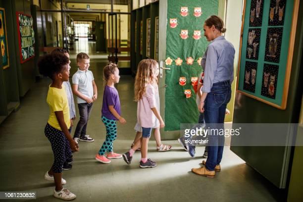maestra feliz bienvenida a los estudiantes de primaria en el aula. - entrando fotografías e imágenes de stock