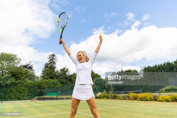 happy female tennis player celebrating the victory on grass court - tennis player stock pictures, royalty-free photos & images