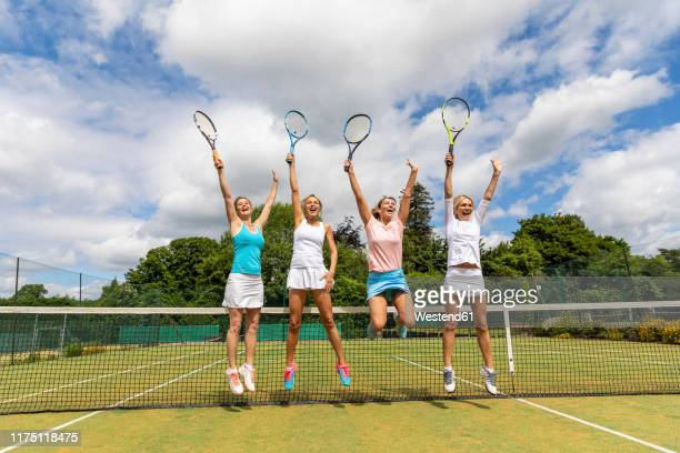 happy female tennis players celebrating the victory on grass court - lawn stock pictures, royalty-free photos & images