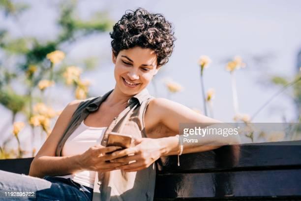 mensajería de texto femenina feliz mientras se sienta en el parque - sin mangas fotografías e imágenes de stock