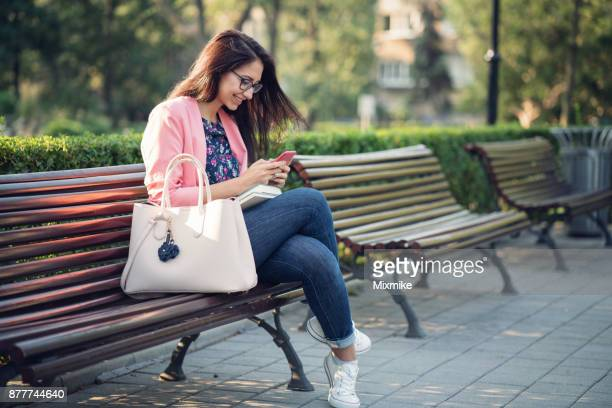 Happy female texting on her phone in the park