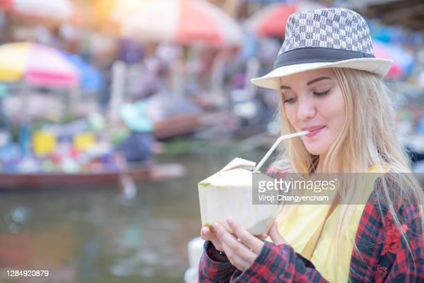 happy female tourist drink fresh coconut at floating market at samut songkhram province, thailand. - 2016 stock pictures, royalty-free photos & images