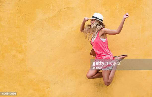Happy female tourist in Cartagena jumping