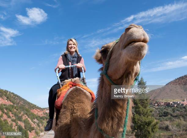 Happy Female Tourist on a Camel in Morocco in North Africa.