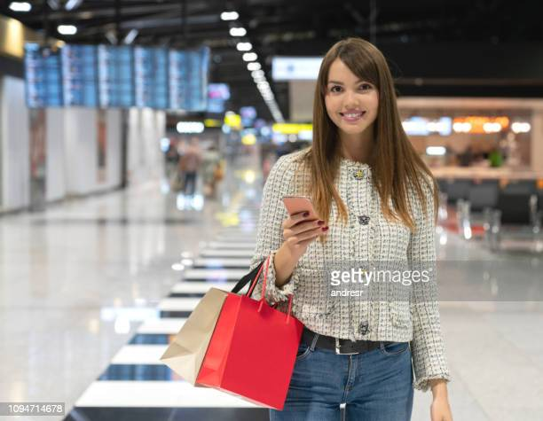 happy female traveler shopping at the airport - duty free stock pictures, royalty-free photos & images