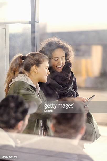 Happy female university students using digital tablet on subway station