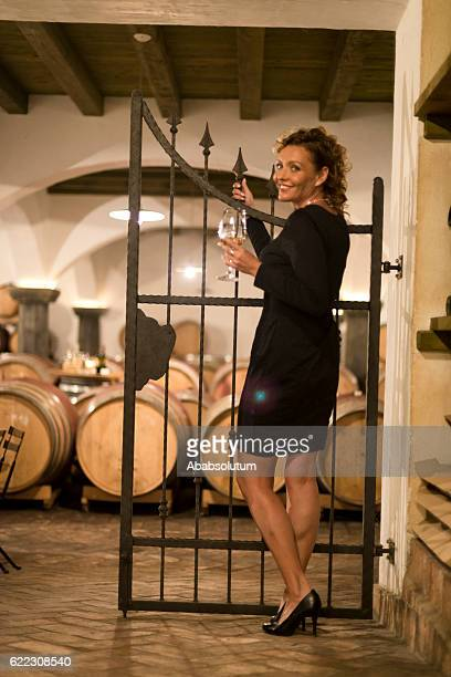 Happy Female Vintner Tasting White Wine, Old Cellar in Europe