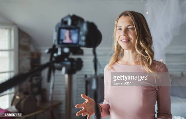 happy female vlogger live streaming from living room - influencer stock pictures, royalty-free photos & images