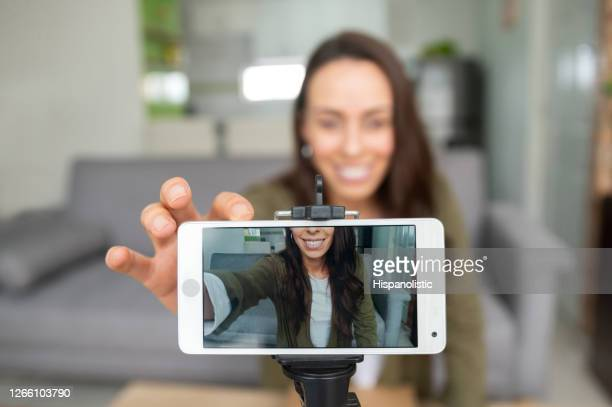 happy female vlogger recording content at home using her cell phone - filming stock pictures, royalty-free photos & images