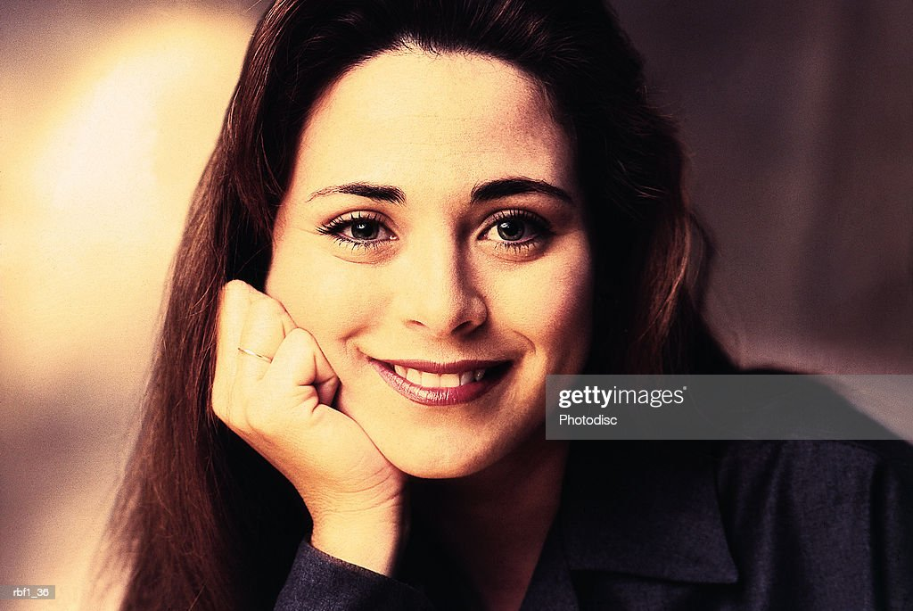 happy female woman with brunette hair wearing a dark shirt rests her chin on her hand while smiling : Stockfoto
