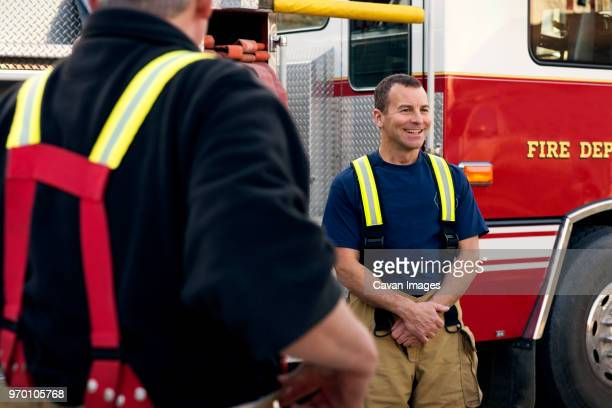 happy fireman standing by coworker against fire engine - fire station - fotografias e filmes do acervo