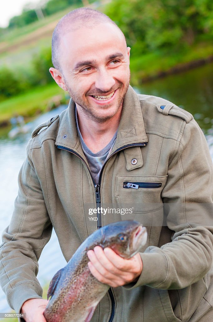 Happy fishing man smiling holding caught Trout fish in hands : Stock Photo