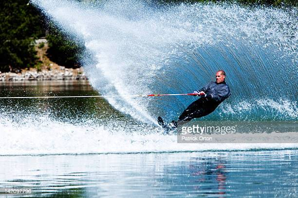 a happy fit man waterskies in a wet suit in idaho. - waterskiing stock photos and pictures