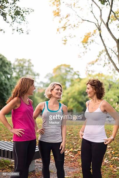 Happy fit women conversing at park