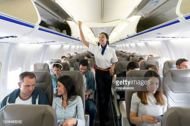 happy flight attendant walking the aisle in an airplane closing overhead compartments - passenger stock pictures, royalty-free photos & images