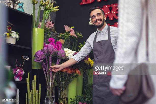 happy florist selling flowers - happy merchant stock pictures, royalty-free photos & images