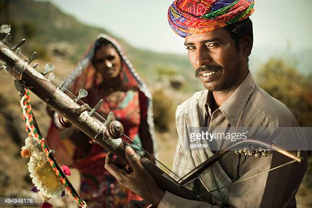 Happy folk musician of Rajasthan, India playing Ravanahatha in hills.