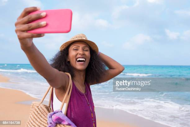 Happy free woman with positive emotion taking selfie on tropical beach.