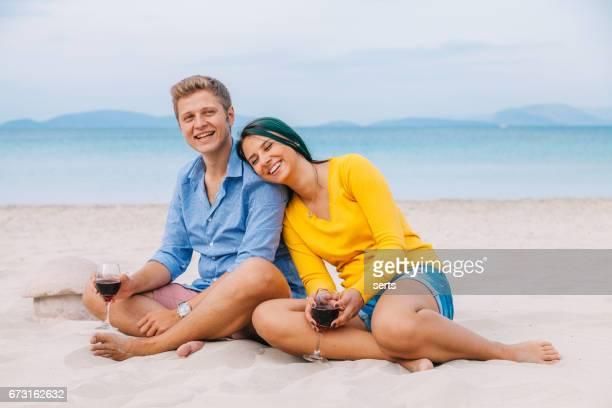 Assis sur la plage de sable l'heureux couple jeune gratuit