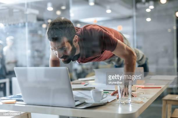 glücklich freier mitarbeiter tun liegestütze und lesen einer e-mail auf einem computer. - kraft stock-fotos und bilder